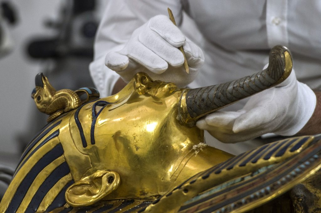 German specialists in restoration work on antiquities in glass and metal Christian Eckmann works on the restoration process of the golden mask of Tutankhamun at the Egyptian Museum in Cairo on October 20, 2015. Egypt started work to remove a crust of dried glue on the beard of legendary boy pharaoh Tutankhamun's golden mask after a botched repair job on the priceless relic. The beard fell off in an August 2014 accident at the Cairo Museum, and was clumsily reattached by employees. Photo credit should read Khaled Desouki/AFP/Getty Images.
