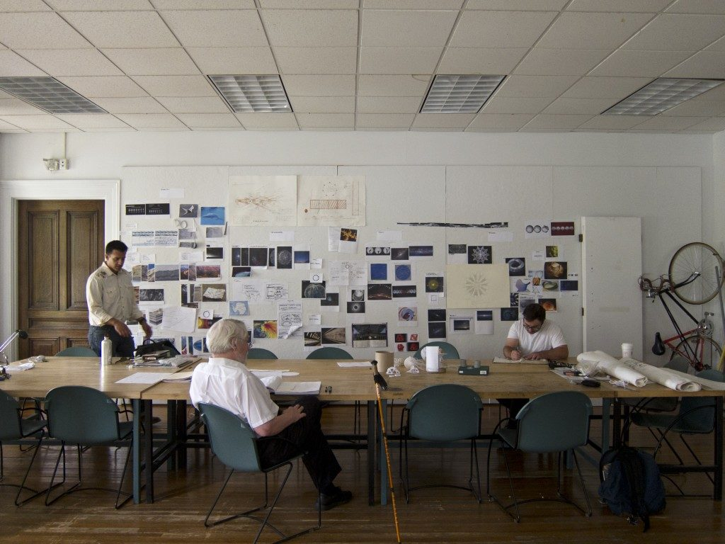 "Lowry Burgess (center) in the Moon Arts ""war room."" Courtesy of the Moon Arts Project."