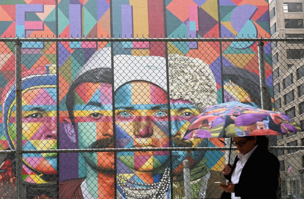 "A woman with an umbrella walks past a mural named ""Ellis Island"" painted by artist Eduardo Kobra, on June 19, 2019 in New York City. Photo: Angela Weiss/AFP/Getty Images."