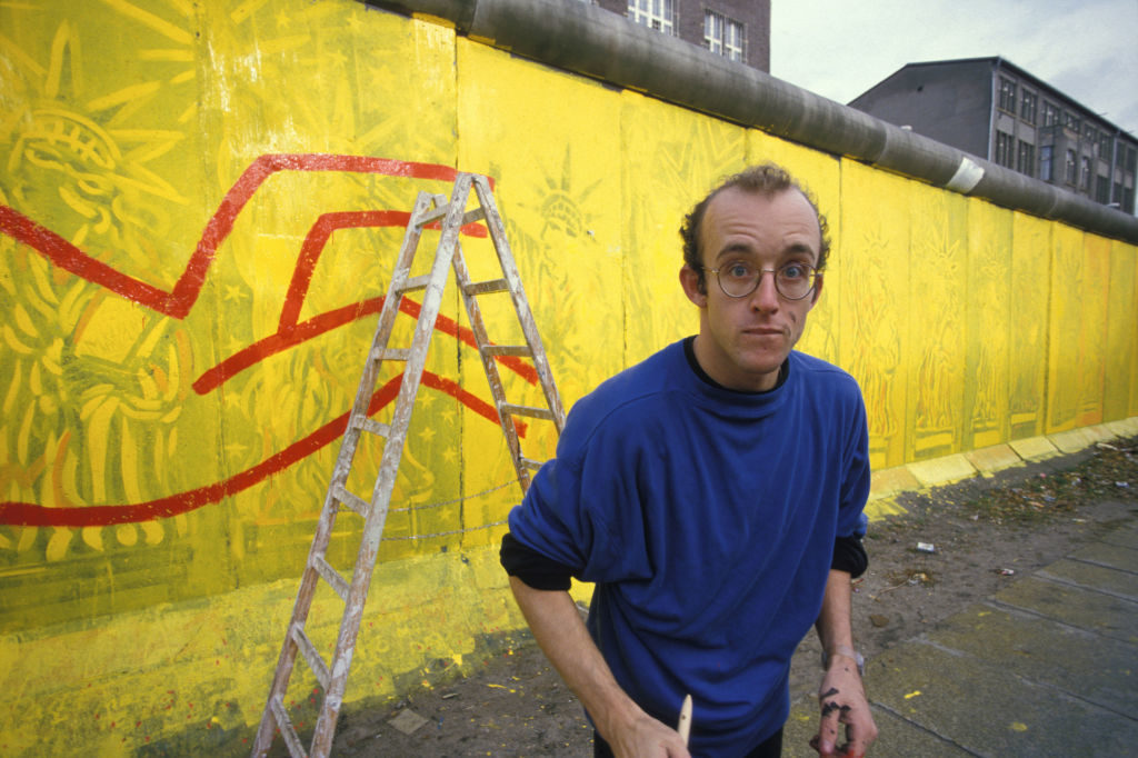 Keith Haring painting on the Berlin Wall in October 1986. Photo by Patrick PIEL/Gamma-Rapho via Getty Images.