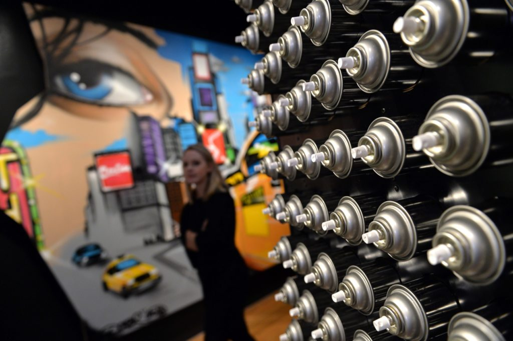 "A wall of spray paint cans constructed for the exhibition ""City as Canvas: GraffitiArt from the Martin Wong Collection"" is seen with <em>Reflections on Times Square #2</em> (2013) by Chris ""DAZE"" Ellis at the Museum of the City of New York February 3, 2014 in New York. Photo courtesy Stan Honda/AFP/Getty Images."