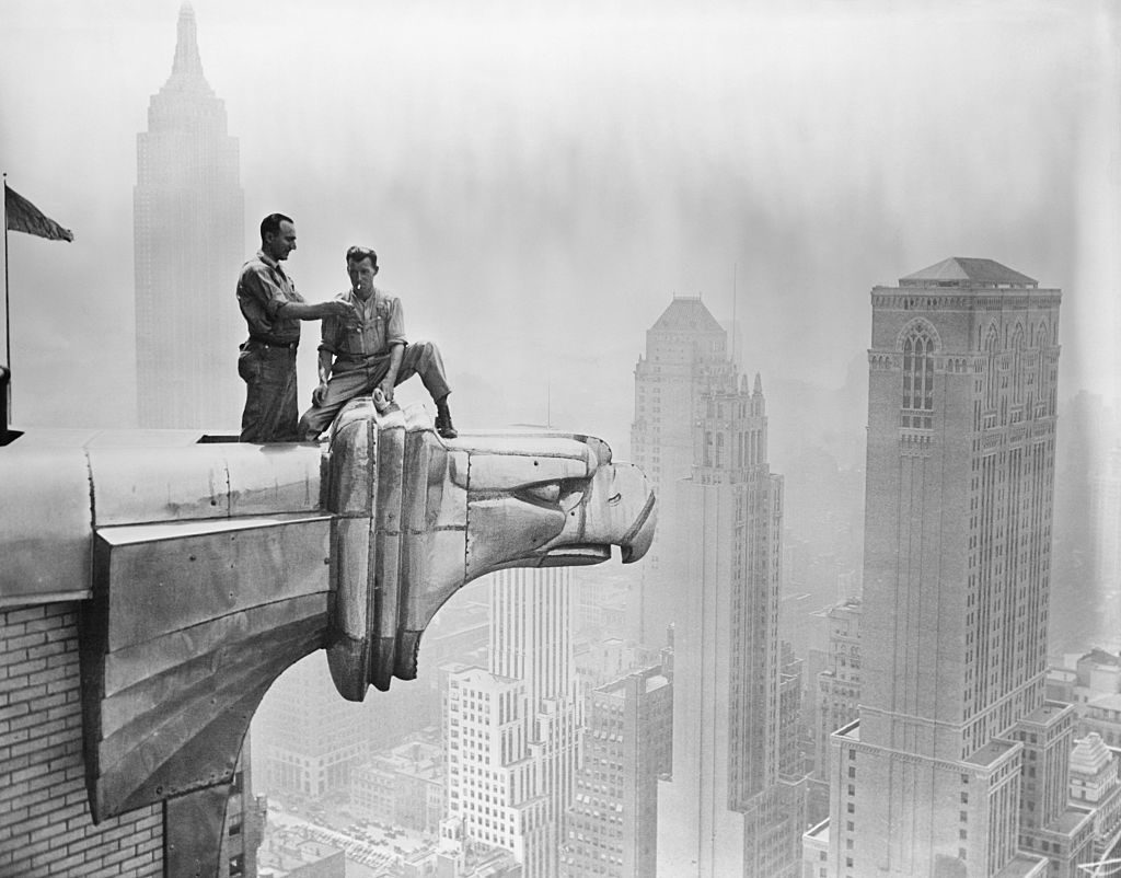 A man lights a fellow worker's cigarette as they take a break on a Chrysler Building gargoyle. Courtesy of Getty Images.