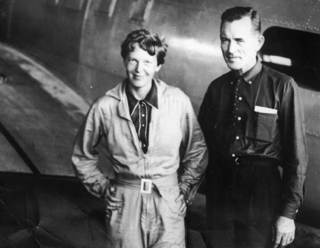 American aviatrix Amelia Earhart with her navigator, Fred Noonan, in the hangar at Parnamerim airfield, Natal, Brazil, June 11, 1937, shortly before their disappearance during their attempted circumnavigation of the globe. Courtesy of Topical Press Agency/Getty Images.