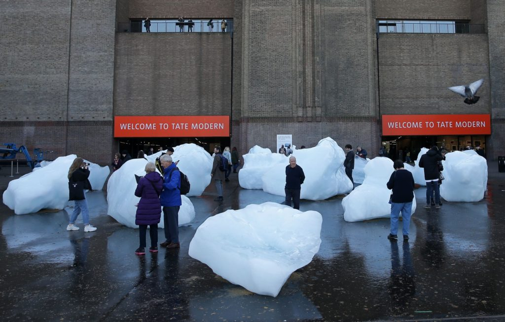 Visitors interact with blocks of melting ice from an exhibit entitled Ice Watch created by Icelandic-Danish artist artist Olafur Eliasson and leading Greenlandic geologist Minik Rosing outside Tate Modern in central London on December 11, 2018. Photo: Daniel Leal-Olivas/AFP/Getty Images.
