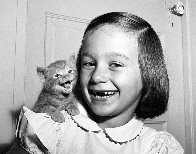 "Walter Chandoha, Paula and Kitten (1955). ""My daughter Paula and the kitten both 'smiled' for the camera at the same time, but the cat's not smiling, he's meowing,"" said Chandoha. Photo courtesy of TASCHEN,©2019 Walter Chandoha."