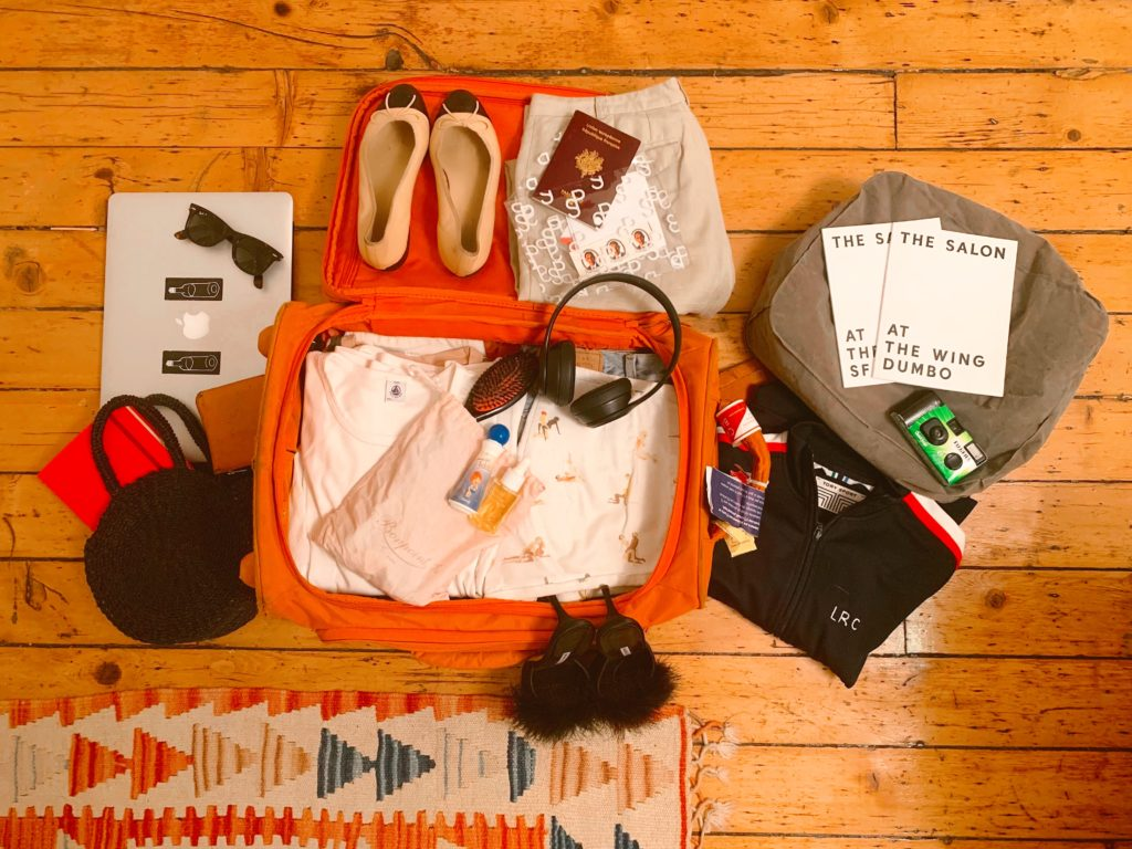 Lolita's suitcase featuring a selection of t-shirts, a pair of Repettos, sunglasses and her inflatable stool. Photo courtesy Lolita Cros.