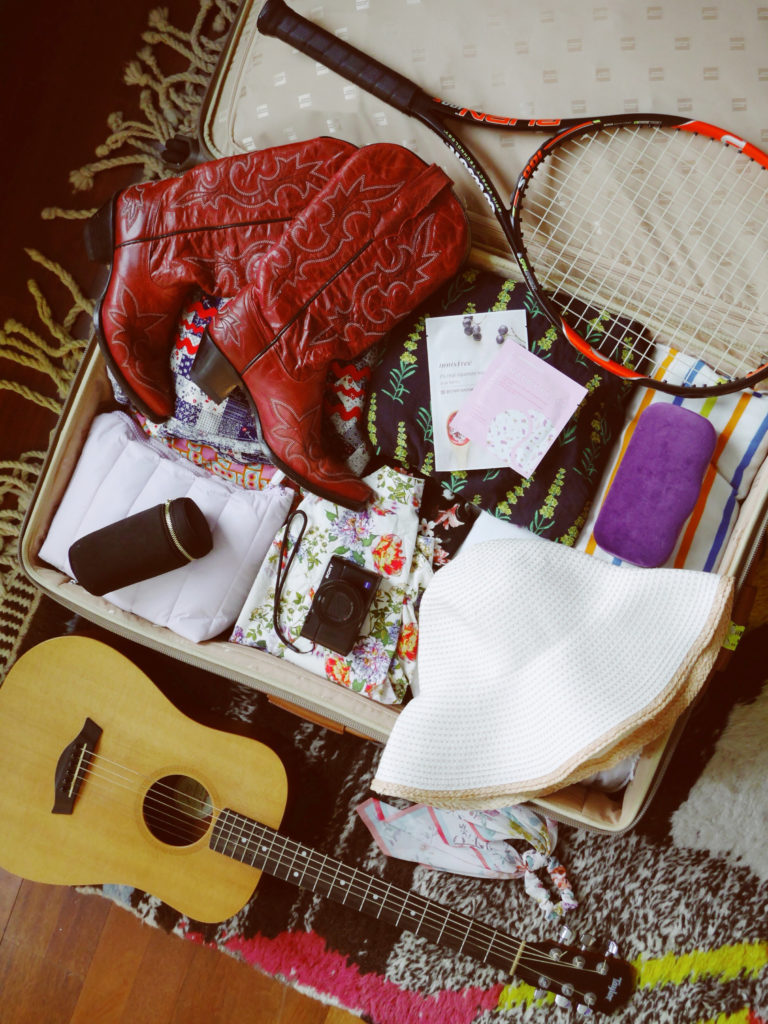 Sophie's suitcase featuring camera lenses, cowboy boots, her guitar and tennis racket. Photo courtesy Sophie Elgort.