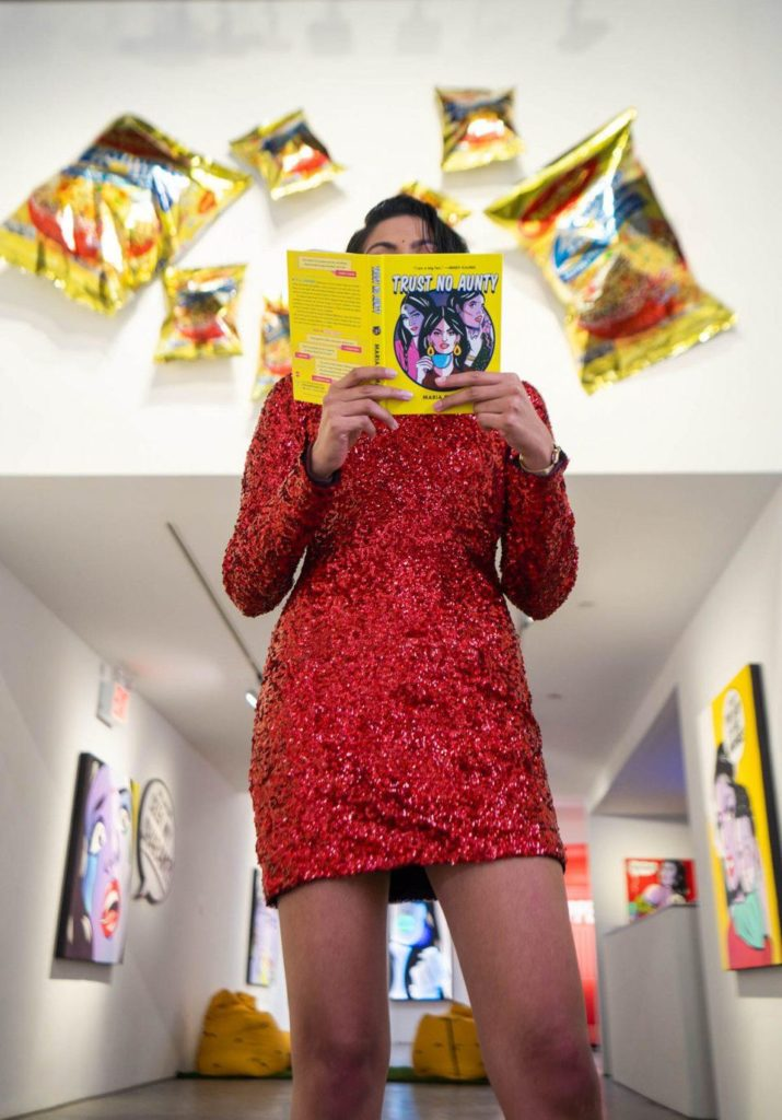 "Maria Qamar with her book <em>Trust No Aunty</em> at her exhibition ""Maria Qamar: Fraaaandship"" at Richard Taittinger Gallery, New York. Photo by Happy Monday."
