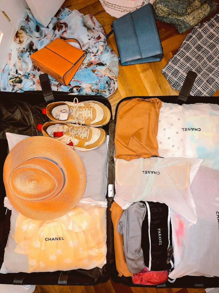 Sarah's suitcase featuring her individually-packed outfits, a panama hat, Nike Mars Yards, and vintage handbags. Photo courtesy Sarah Hoover.